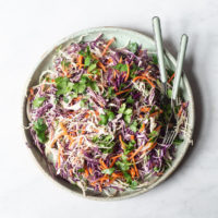 a plate filled with creamy Mexican coleslaw sitting on a marble surface