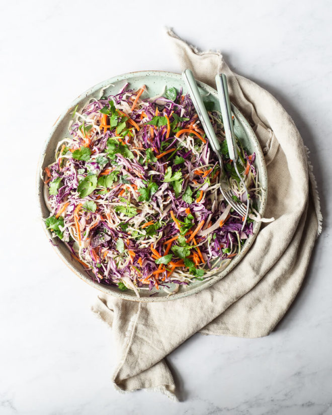 a plate filled with creamy Mexican coleslaw sitting on a tan kitchen towel on a marble surface