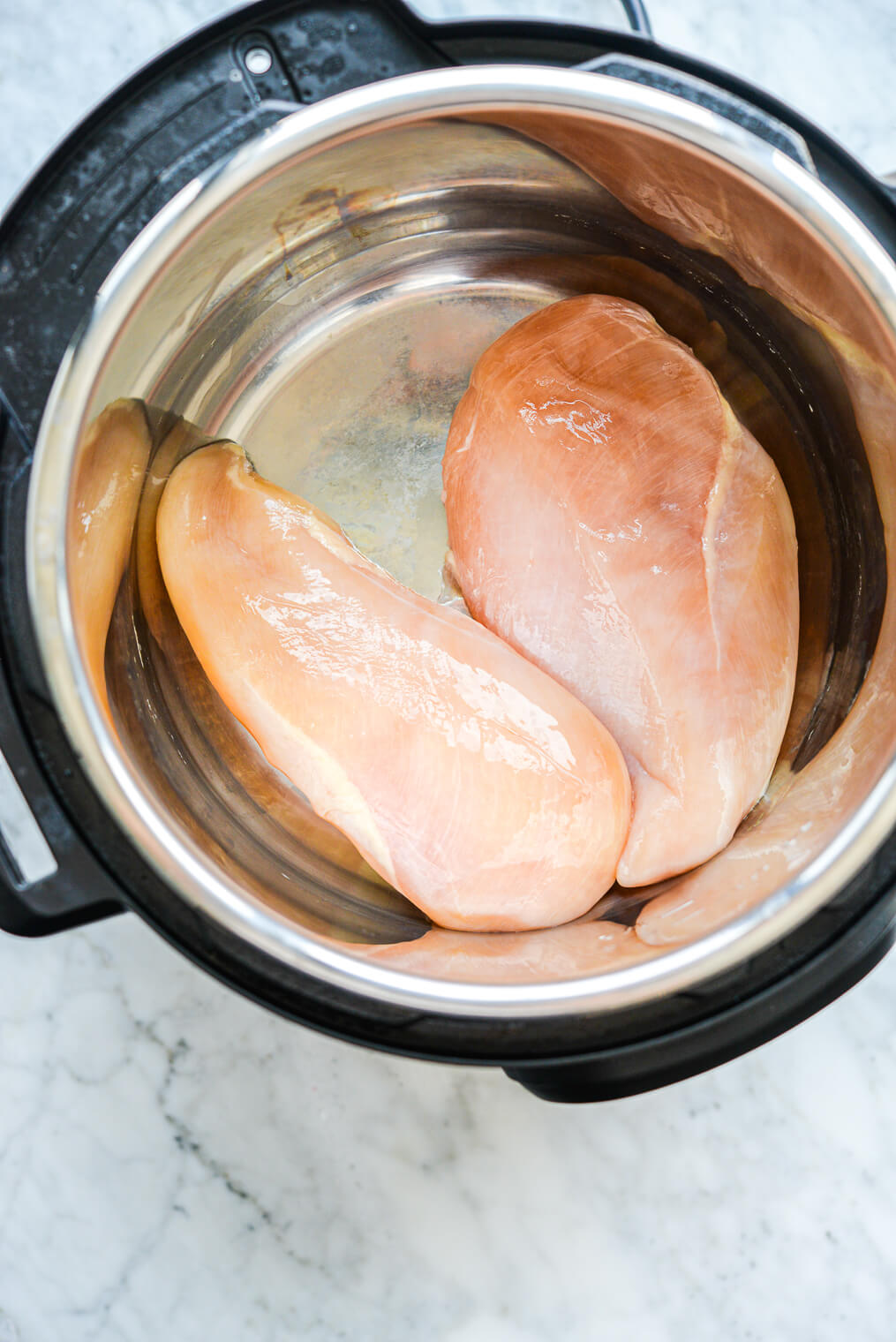 two raw chicken breasts in an instant pot