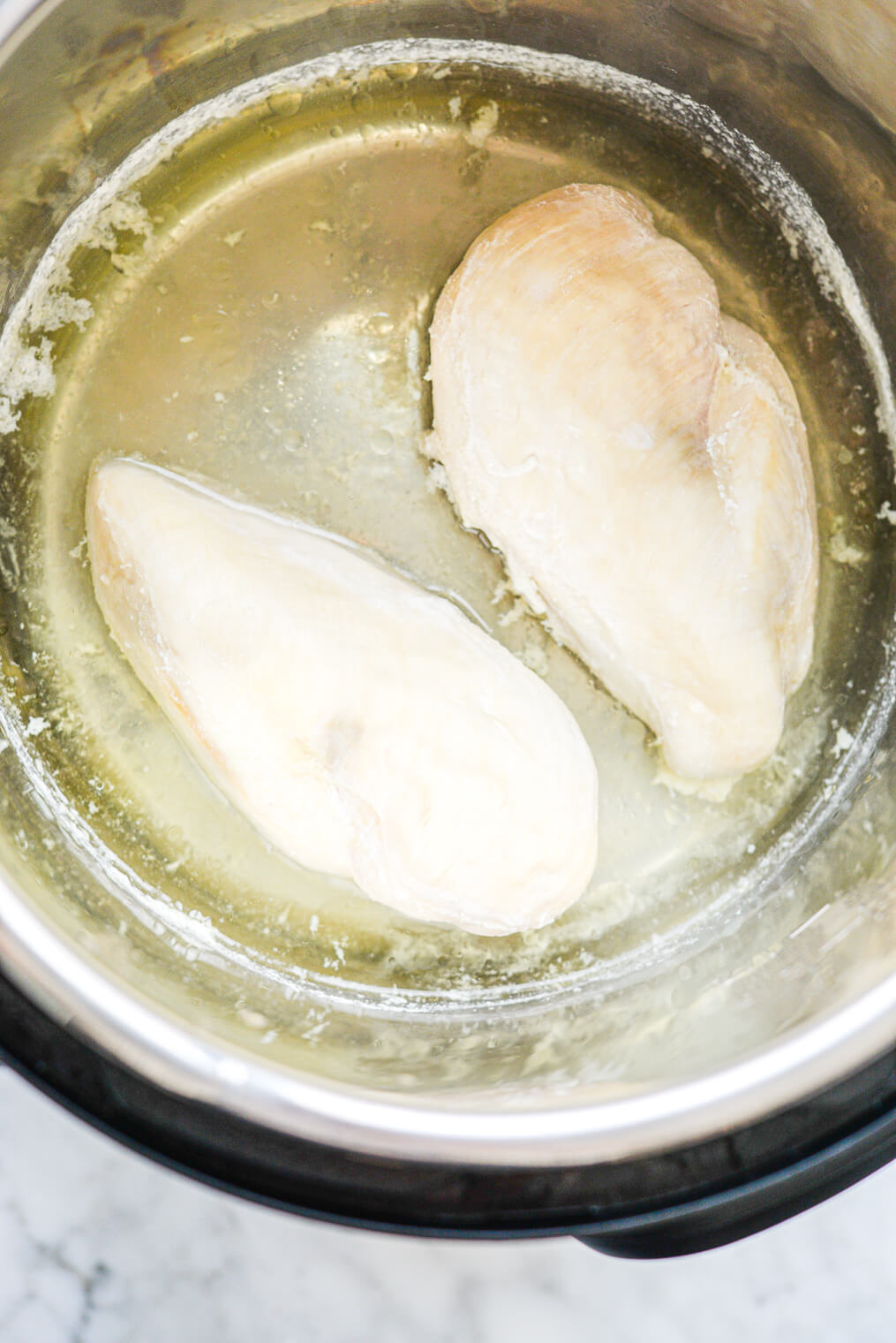 two cooked chicken breasts in an instant pot