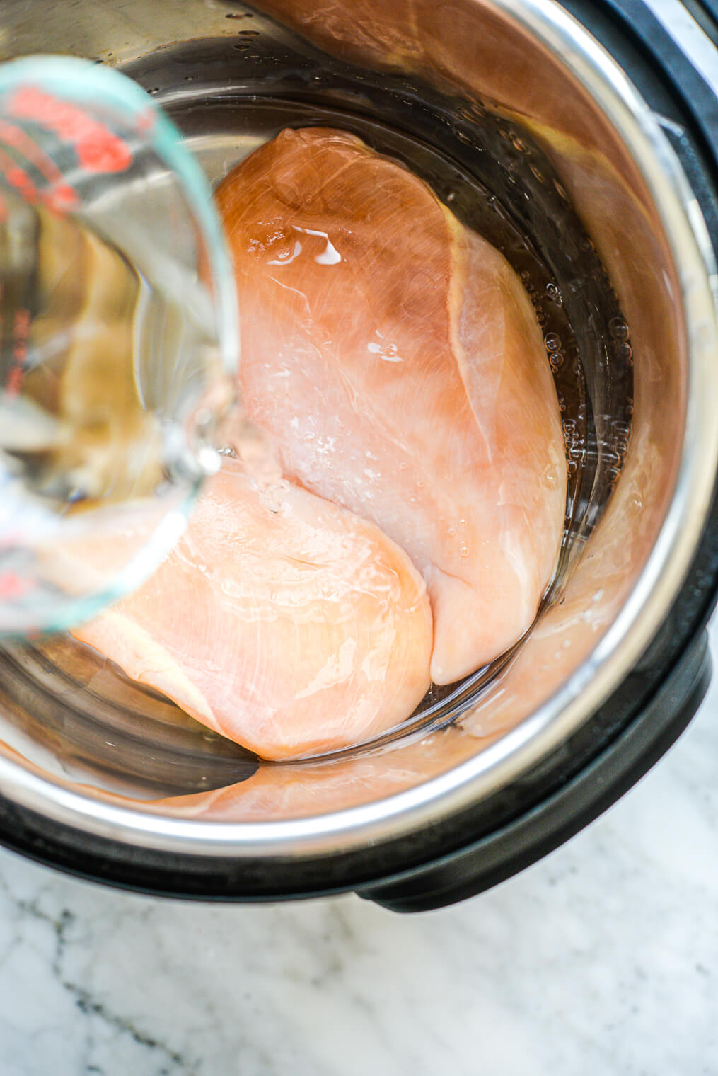 a person pouring a cup of water over two raw chicken breasts in an instant pot