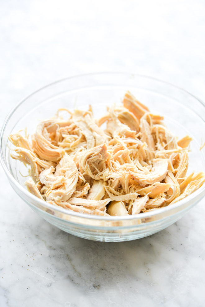shredded chicken in a clear glass bowl on a marble surface