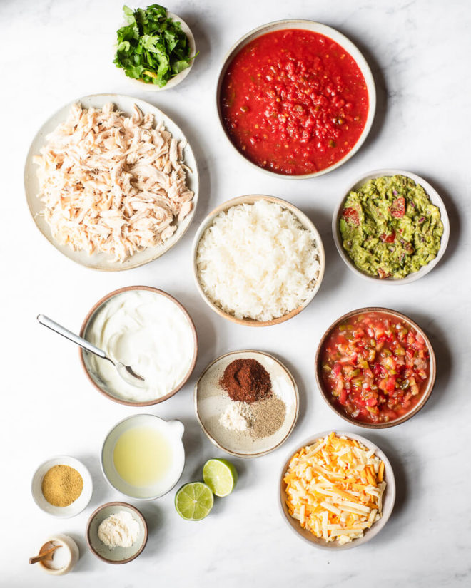 all of the ingredients for chicken taco casserole sitting in different sized bowls and plates on a marble surface