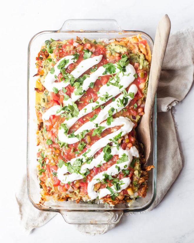 a full serving dish of chicken taco casserole with a garnish of sour cream and cilantro on top
