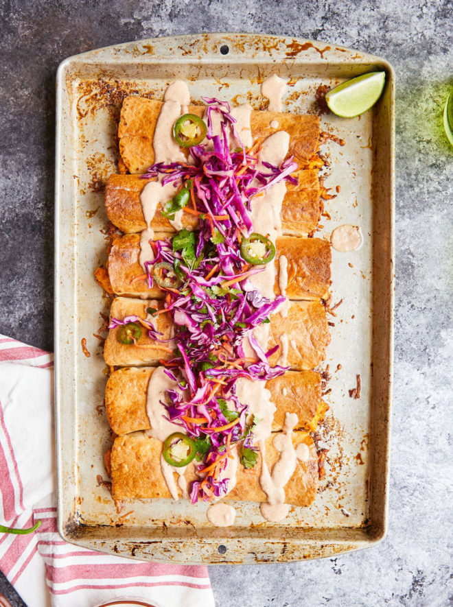chicken chimichangas topped with a creamy light orange sauce and a bright purple cabbage slaw on a sheet pan on a dark grey surface