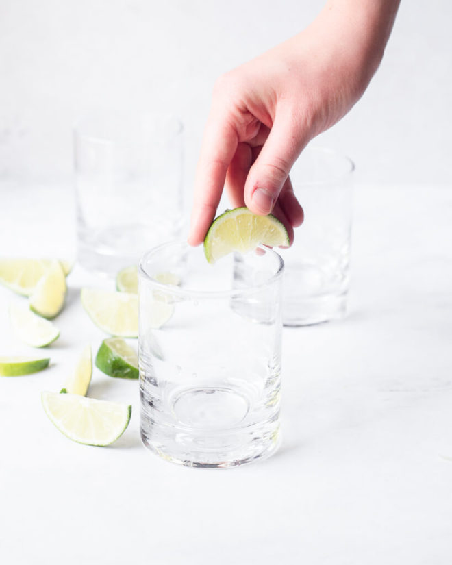 a person's hand squeezing lime juice over the rim of a glass