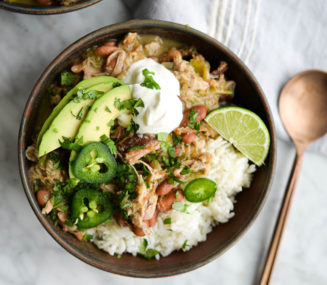 two bowls of pork chili verde over white rice on a marble surface