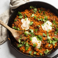 a cast iron skillet of shredded carrot breakfast hash topped with 3 fried eggs
