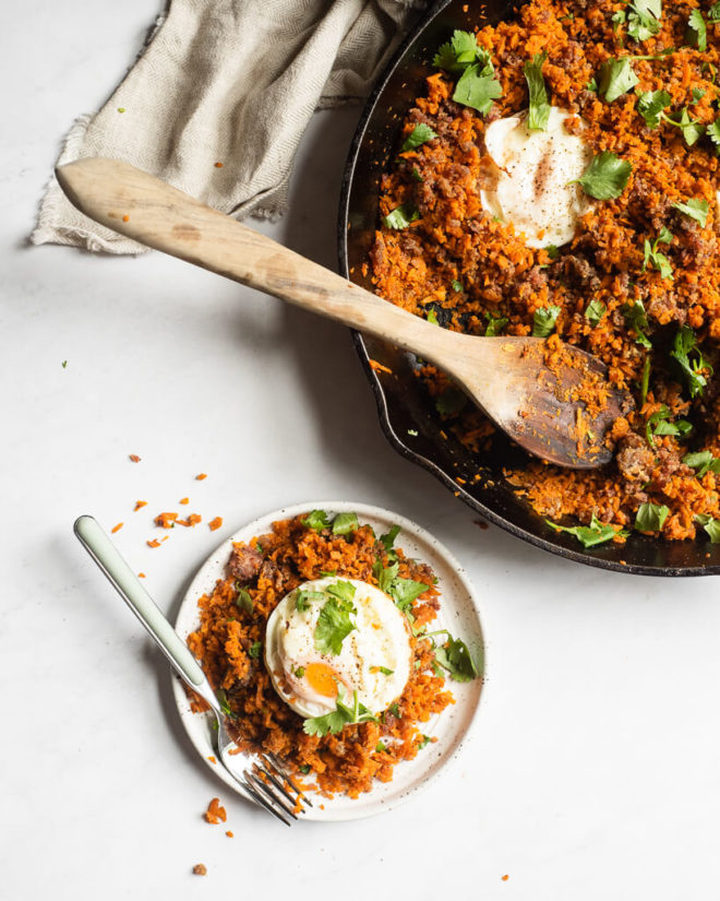 a cast iron skillet of shredded carrot breakfast hash with one serving scooped out on a small plate sitting next to it