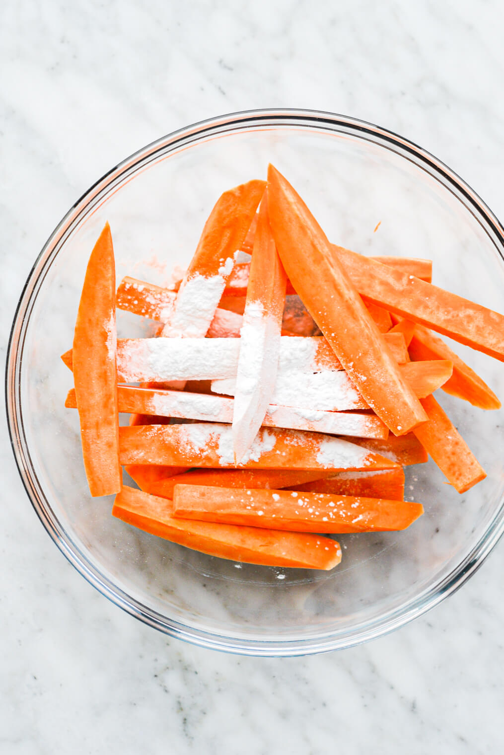 a clear glass bowl of fry-cut sweet potatoes with a teaspoon of arrowroot starch over top them