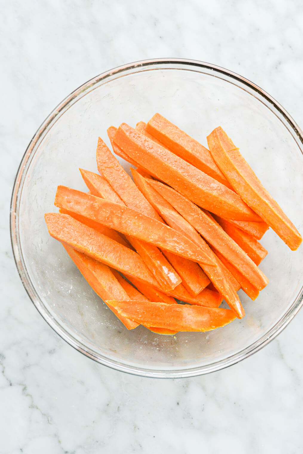 a clear glass bowl of fry-cut sweet potatoes coated in arrowroot starch