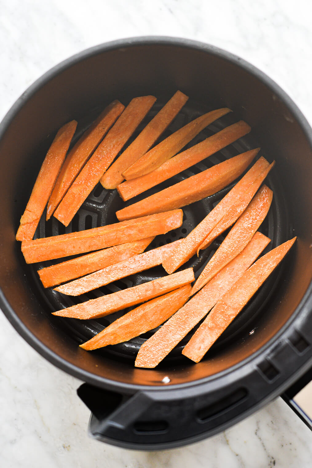 raw sweet potato fries in the basket of an air fryer