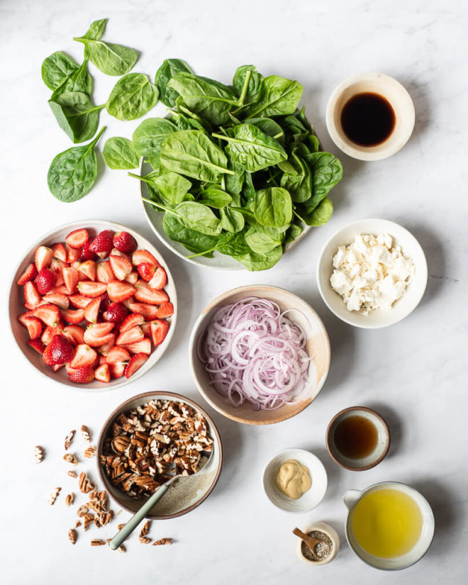 the ingredients for strawberry spinach salad (spinach, pecans, strawberries, goat cheese, red onion, and dressing ingredients)