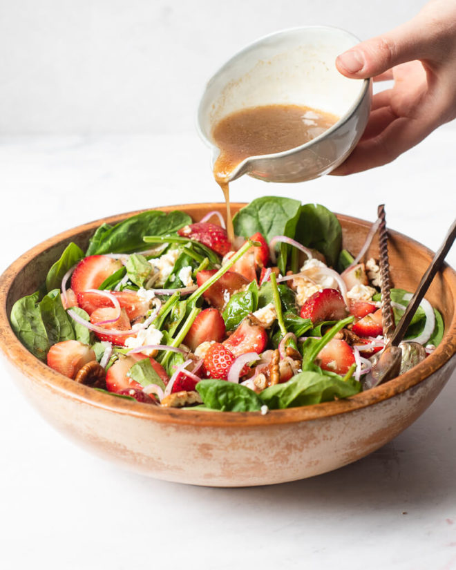 a large wooden bowl of strawberry spinach salad with two large spoons sticking out of it and a woman pouring dressing over top of it