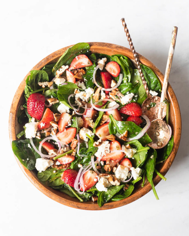 a large wooden bowl of strawberry spinach salad with two large spoons sticking out of it