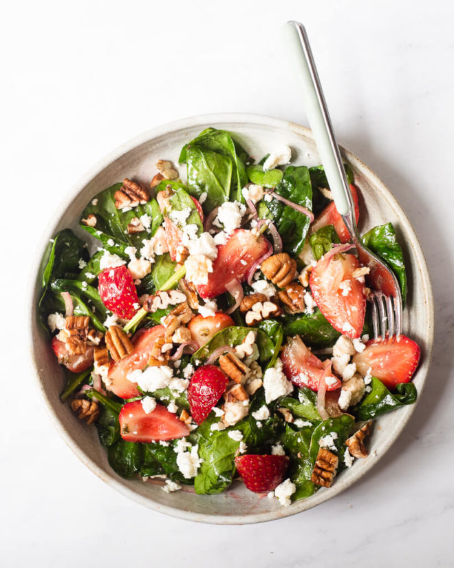 a shallow bowl filled with strawberry spinach salad