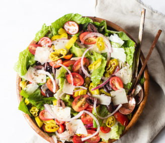 an italian salad loaded with red onions, parmesan cheese, cherry tomatoes, and olives sitting in a bowl