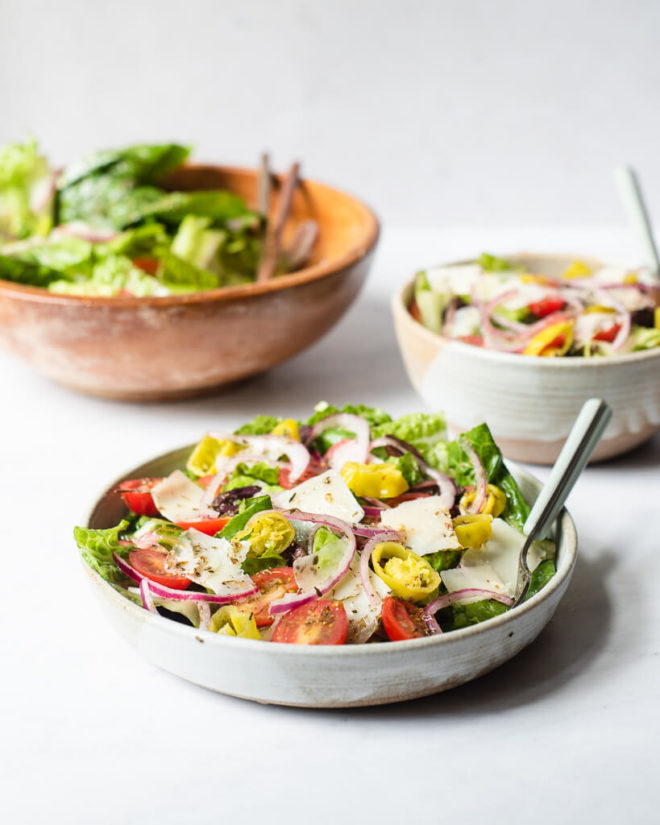 an italian salad loaded with red onions, parmesan cheese, cherry tomatoes, and olives sitting on a small bowl with a fork sticking out of it