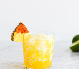a margarita glass with a pineapple margarita on the rocks in it garnished with a pineapple wedge dipped in chili salt
