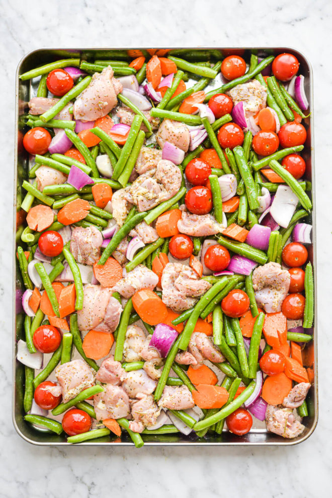a sheet pan chicken thighs and veggies dinner before going into the oven (raw) -- green beans, carrots, onions, tomatoes, and chicken thighs