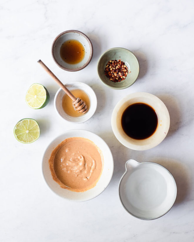 all of the ingredients for peanut dressing in different sized bowls and plates on a marble surface