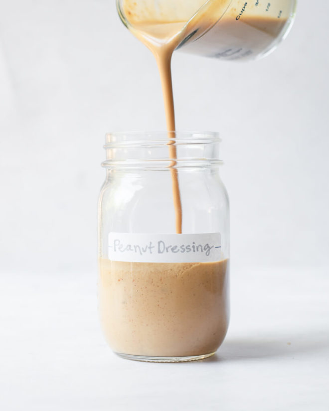 a person pouring peanut dressing into a labeled mason jar