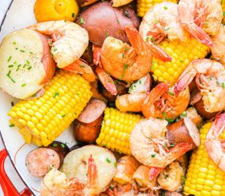 a large, shallow bowl of corn, shrimp, sausage, and potatoes (a shrimp boil)