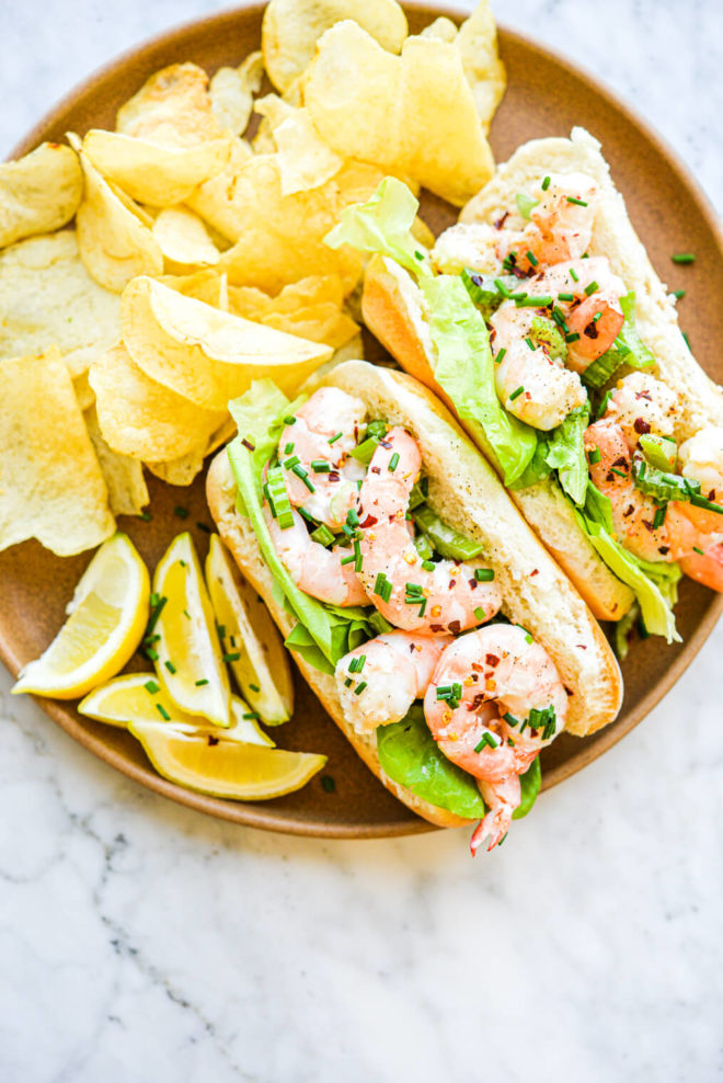 two rolls of bread filled with lettuce leaves and a boiled shrimp salad on a plate next to potato chips and lemon wedges