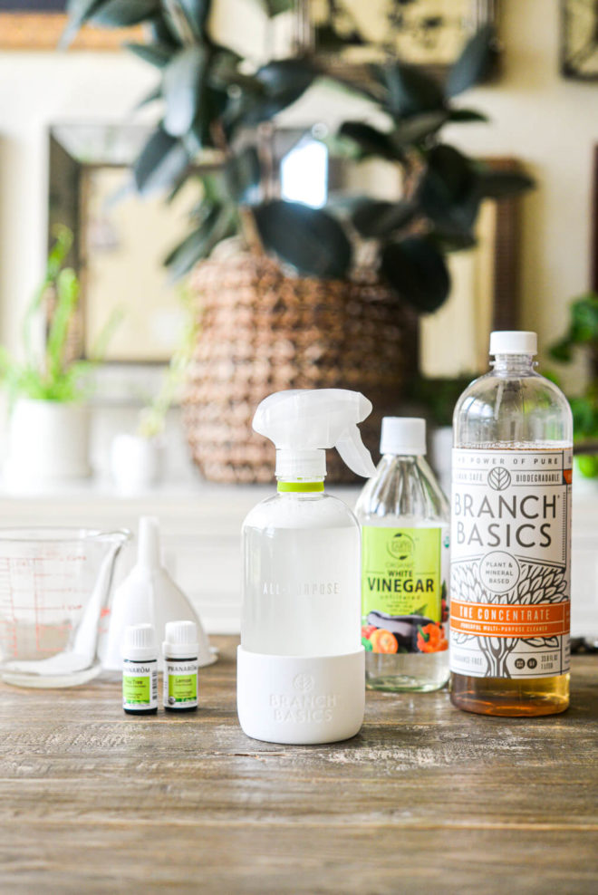 the ingredients for all purpose cleaner: branch basics concentrate, essential oils, and white vinegar sitting on a kitchen table
