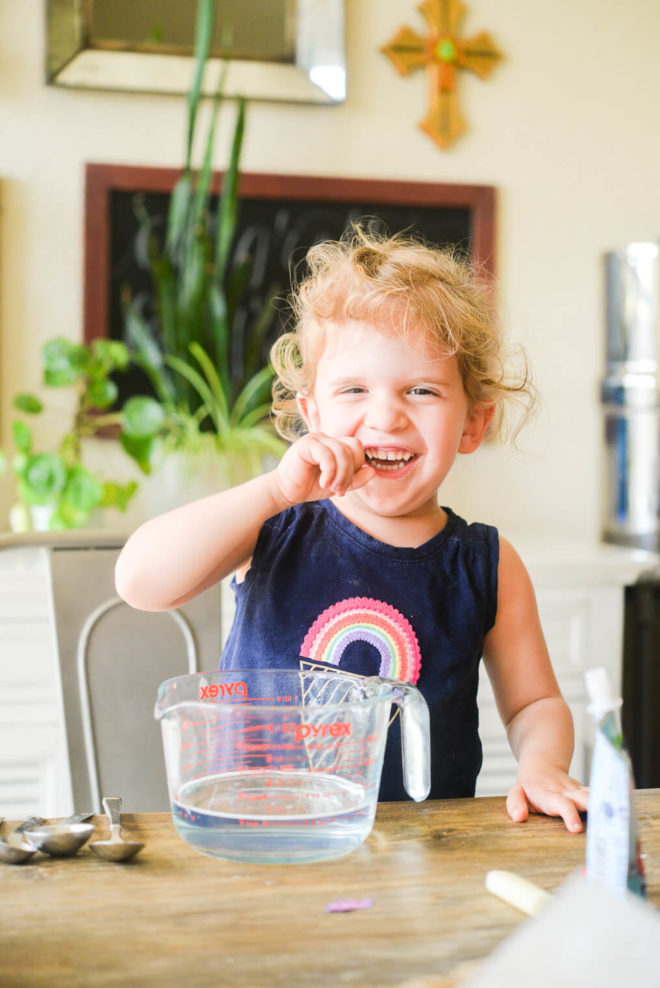 a little girl sitting at the table with a large measuring cup of safe, non toxic all purpose cleaner in front of her