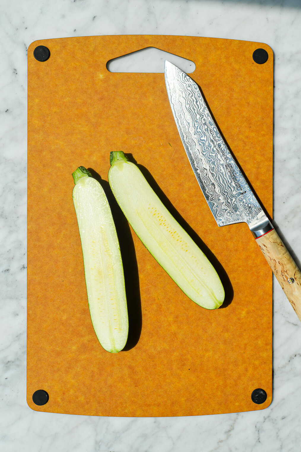 a cutting board with a raw halved zucchini sitting next to a knife