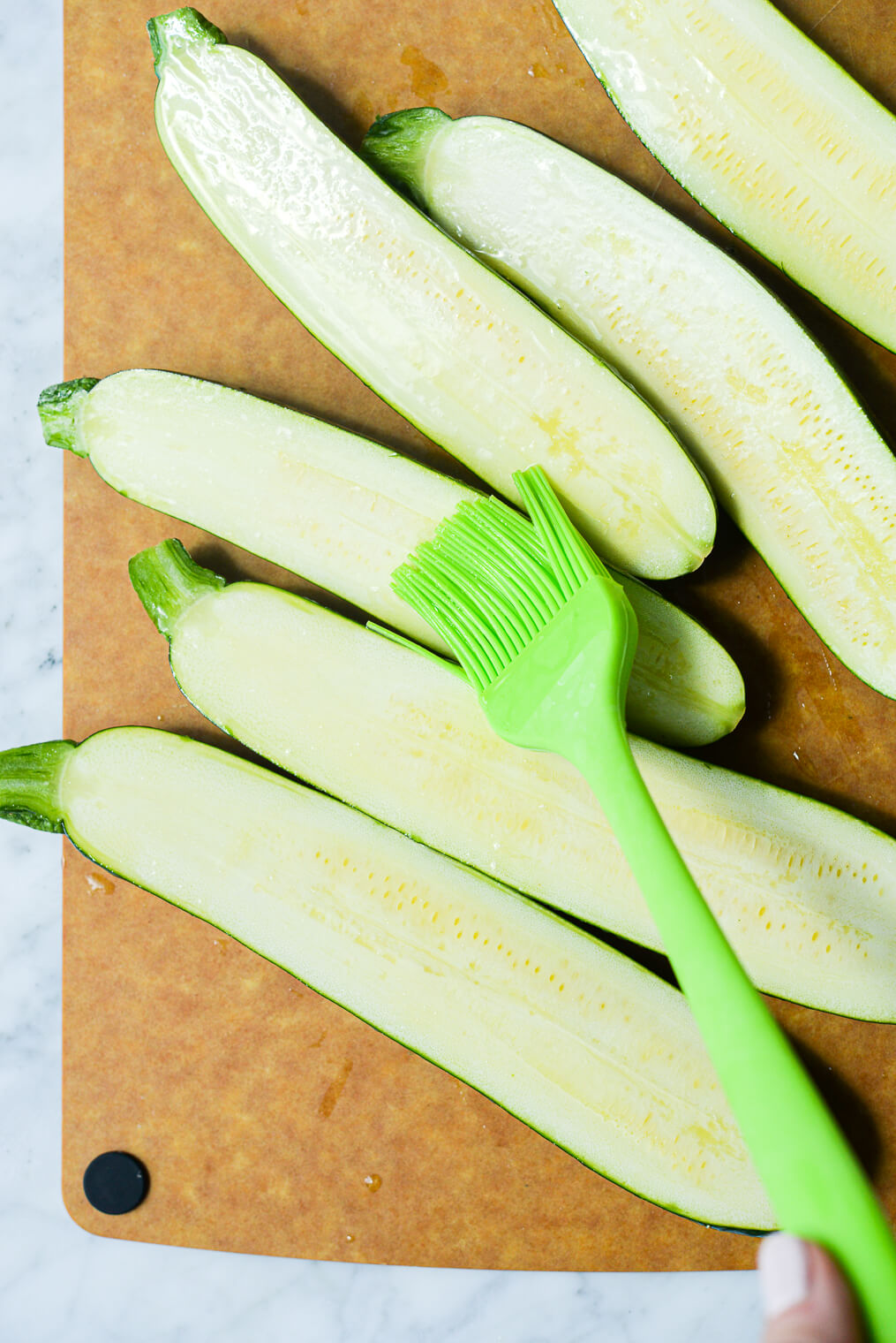 6 halves of zucchini being rubbed with olive oil using a basting brush