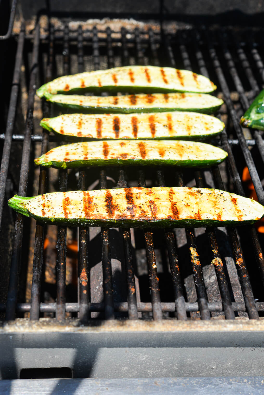 5 halves of zucchini with grill marks sitting on the grates of a gas grill