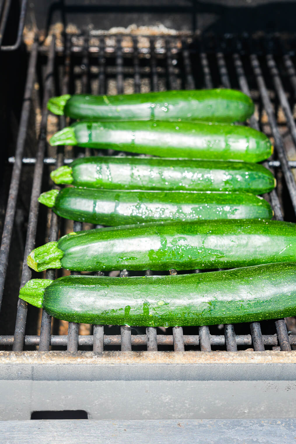 6 halves of zucchini, cut side down, laying on the grates of a gas grill