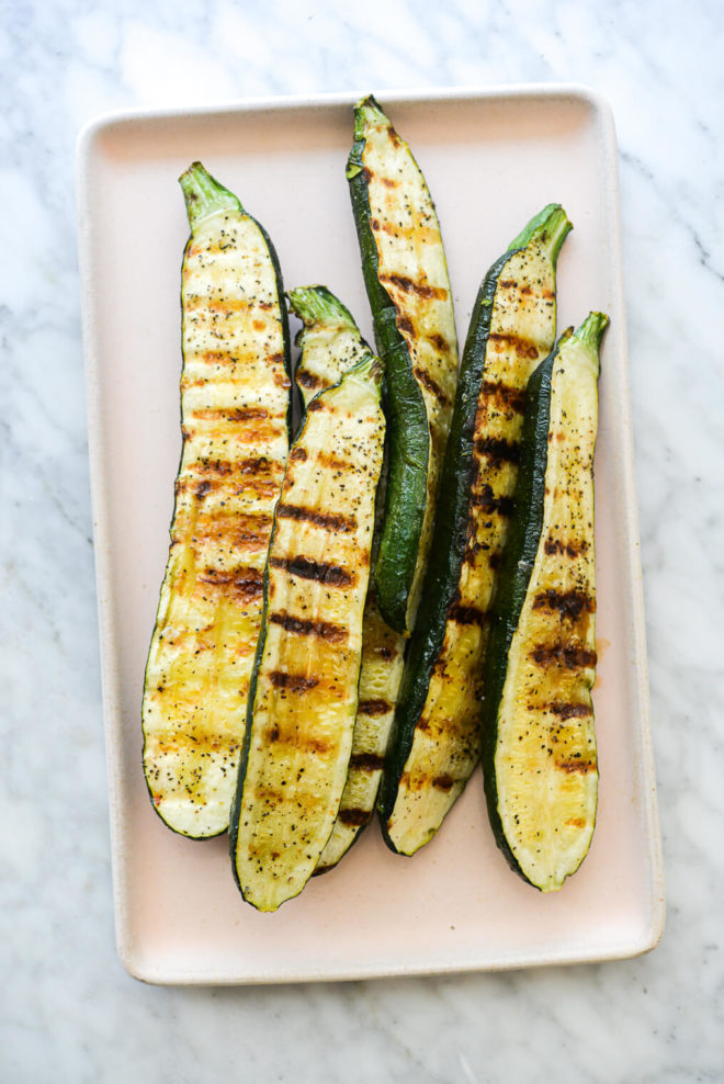 5 grilled zucchini halves on a pink rectangular plate