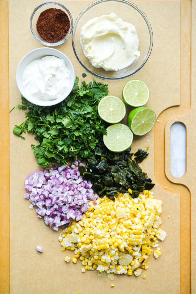 all of the ingredients for a mexican street corn salad in groups on a very large cutting board
