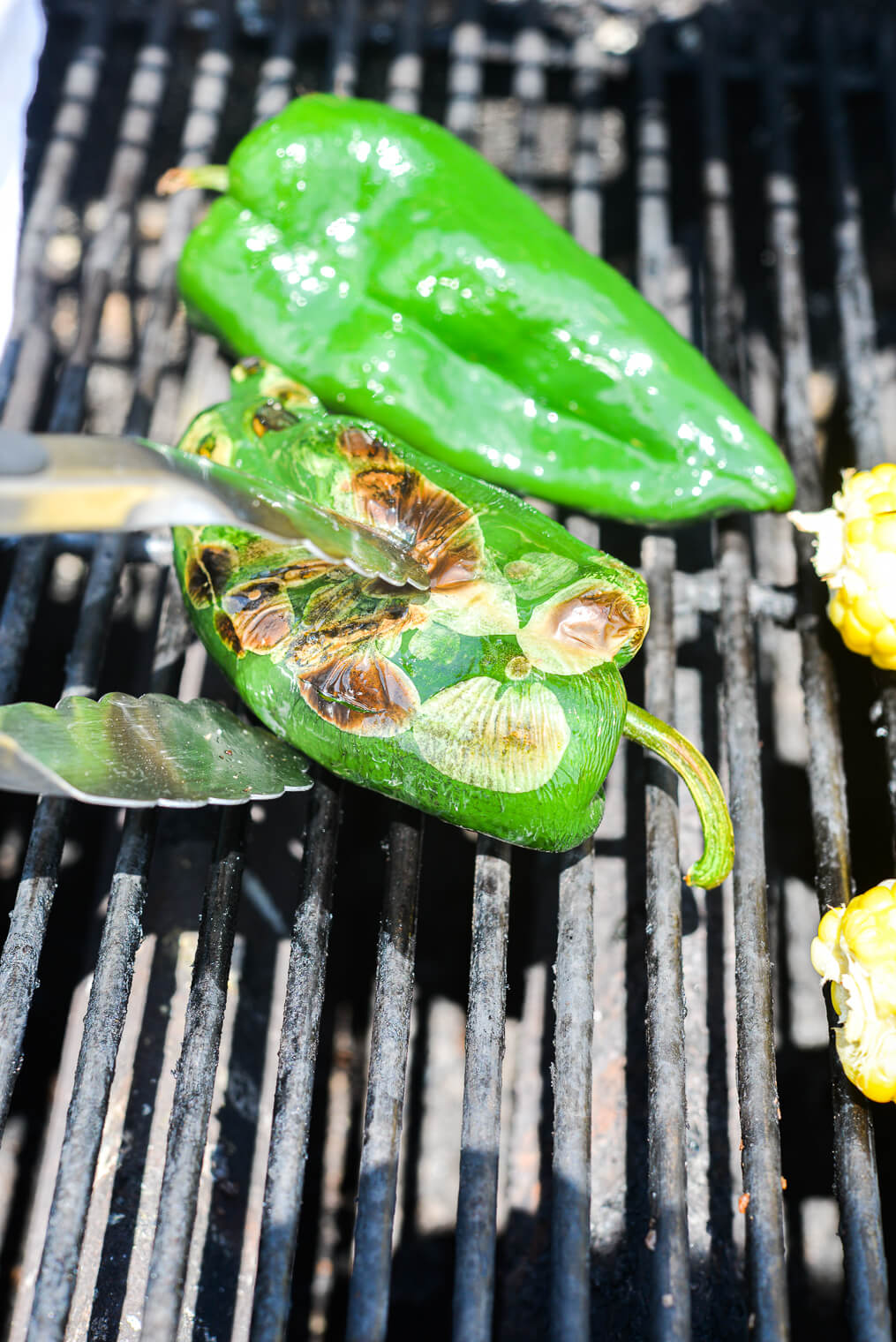 2 blistered poblano peppers on the grates of a gas grill