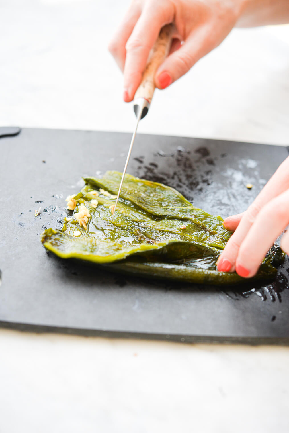 a person using a knife to scrape the seeds out of charred poblano peppers