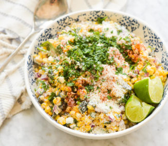 a bowl of mexican street corn salad garnished with cotija cheese, cilantro, lime wedges, and tajin