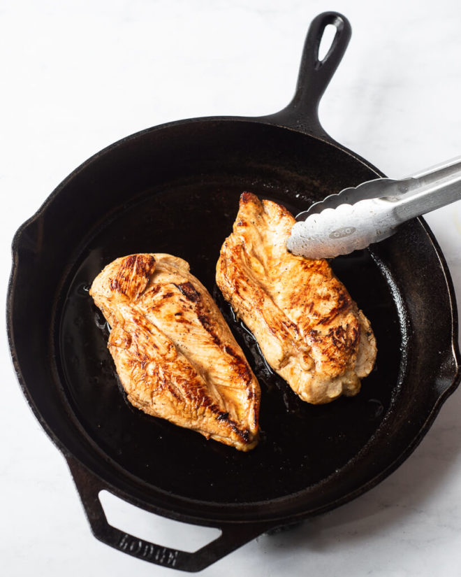 a person using tongs to grab one seared chicken breast (that's sitting next to another seared chicken breast) from a cast iron skillet