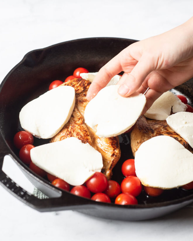 a person placing fresh sliced mozzarella over top a cast iron skillet with seared chicken breasts and cherry tomatoes