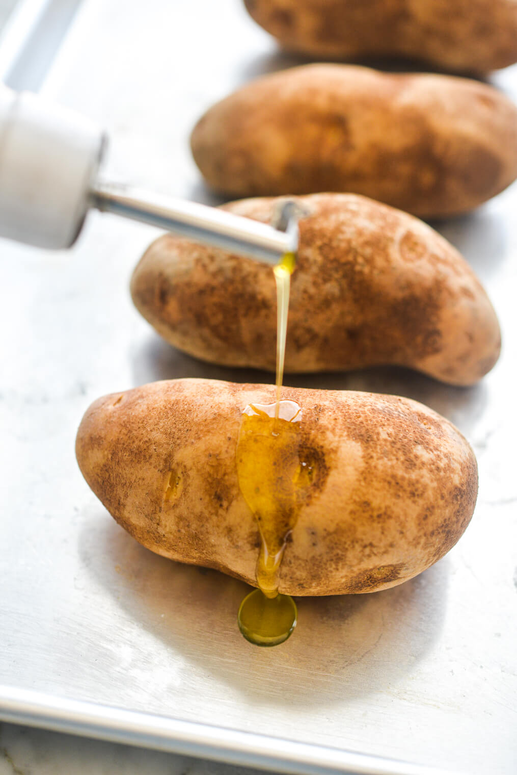 4 raw russet potatoes being drizzled with olive oil on a metal sheet pan