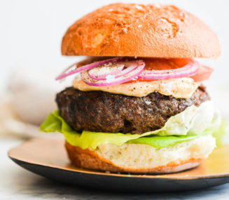 a beef burger on a bun topped with lettuce, tomato, red onion, and chipotle mayo