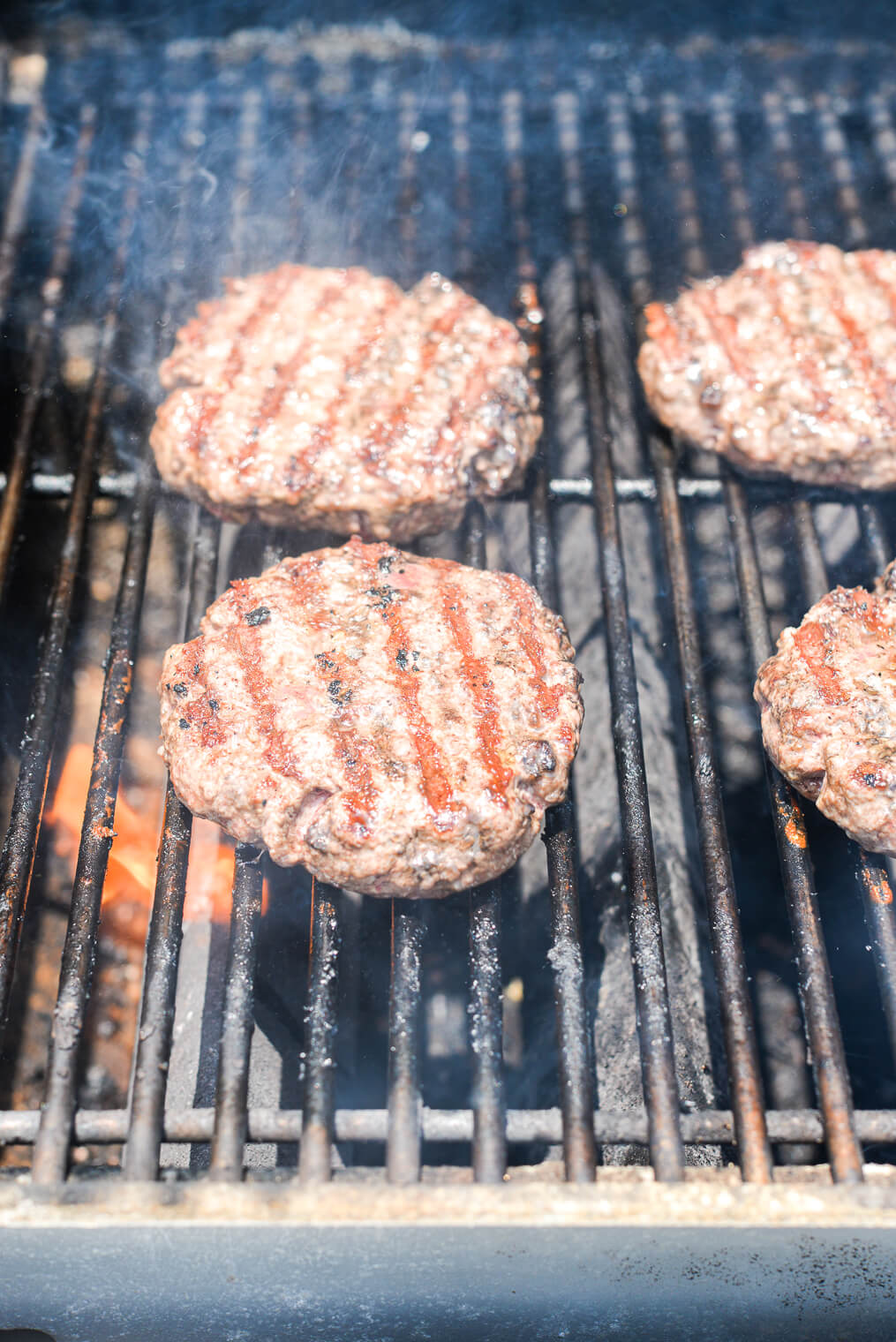 4 ground beef patties on the grill grates of a gas grill