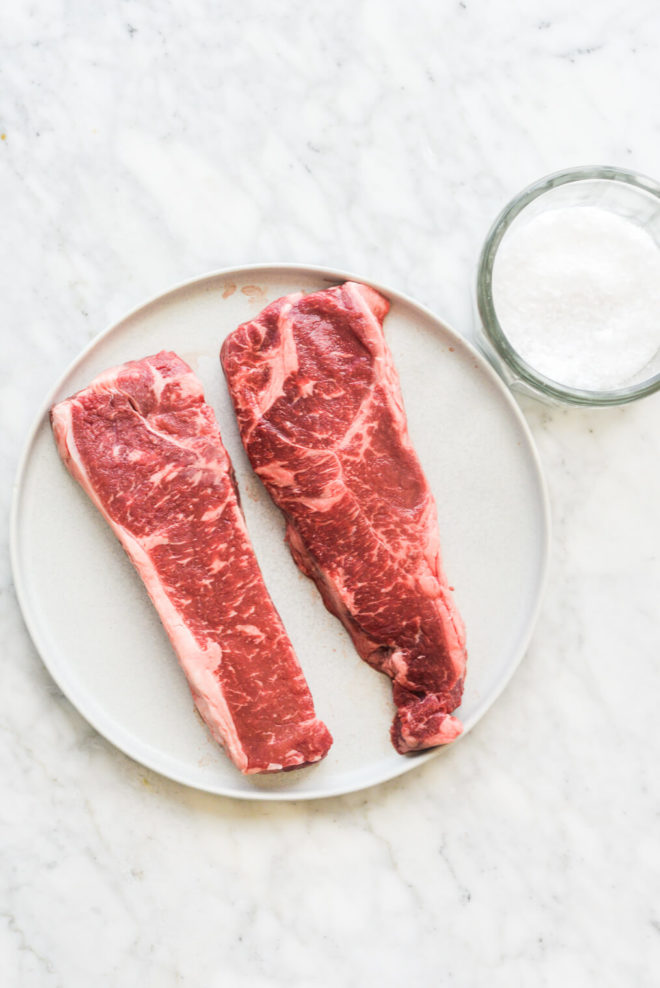 two raw steaks sitting on a plate next to a bowl of coarse sea salt