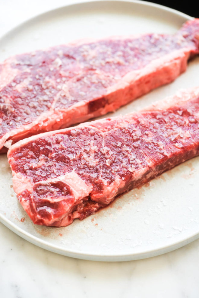 two steaks that have been heavily salted sitting on a plate