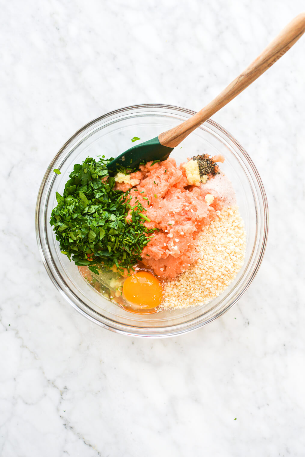 a large glass bowl with food processed salmon, breadcrumbs, an egg, herbs, and some seasonings