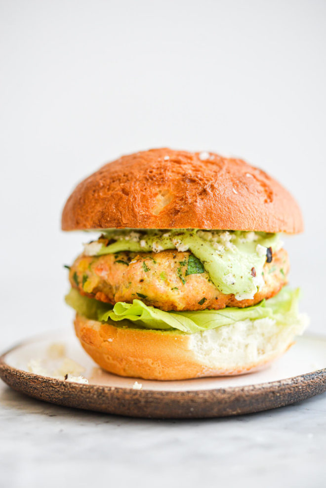 a salmon burger on a bun with lettuce and green goddess dressing