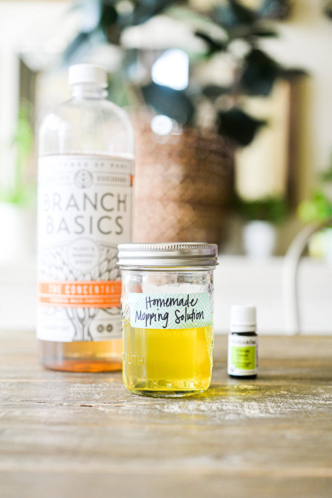 a bottle of Branch Basics Concentrate, essential oil, and a mason jar of mopping solution sitting on a wooden kitchen table