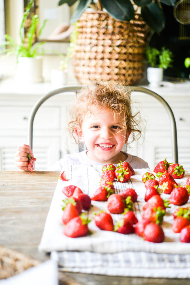 a little girl sitting down at a table and smiling behind a bunch of strawberries spread out on a kitchen towel